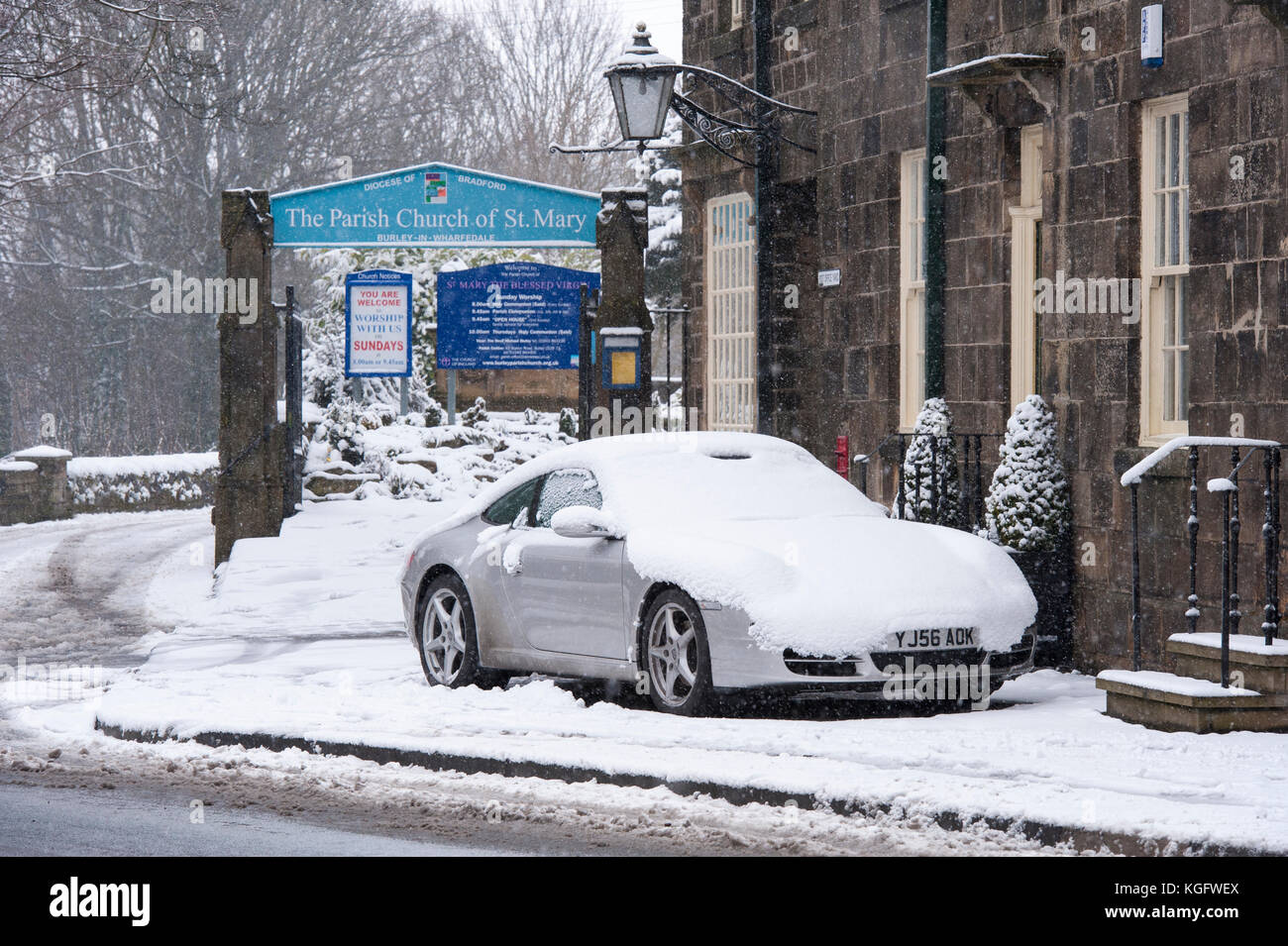 Cold, snowy winter day with snow-covered car parked outside stone cottages & church gate in village - Burley-in Stock Photo