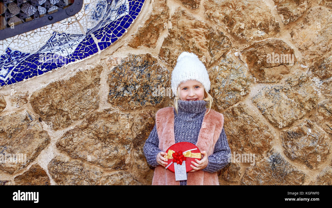 Winter wonderland in Barcelona at Christmas. Full length portrait of happy elegant child in Barcelona, Spain holding - Stock Image