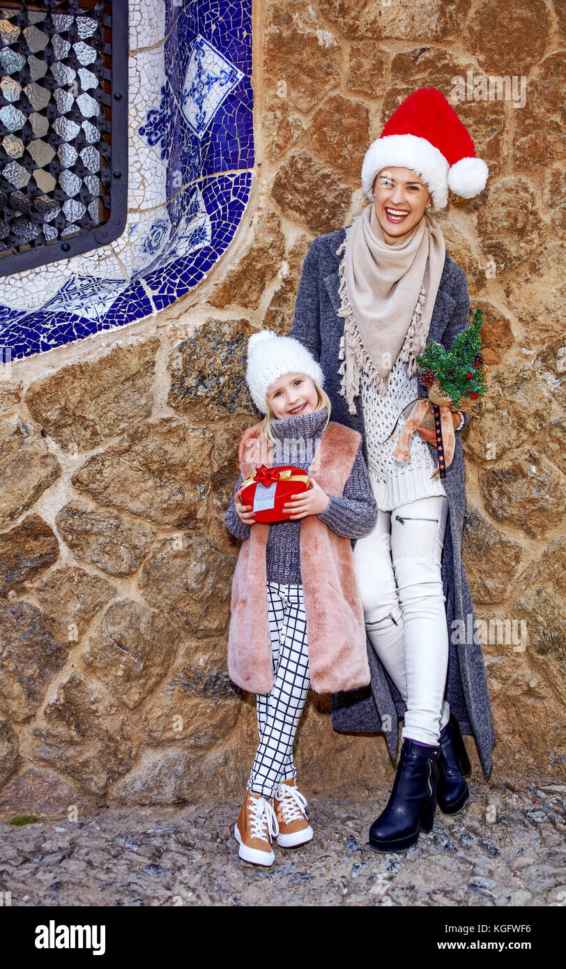 Winter wonderland in Barcelona at Christmas. young mother and daughter tourists in a Santa hat in Barcelona, Spain - Stock Image