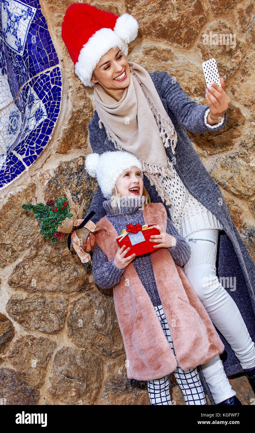 Winter wonderland in Barcelona at Christmas. young mother and daughter travellers in a Santa hat at Guell Park in - Stock Image