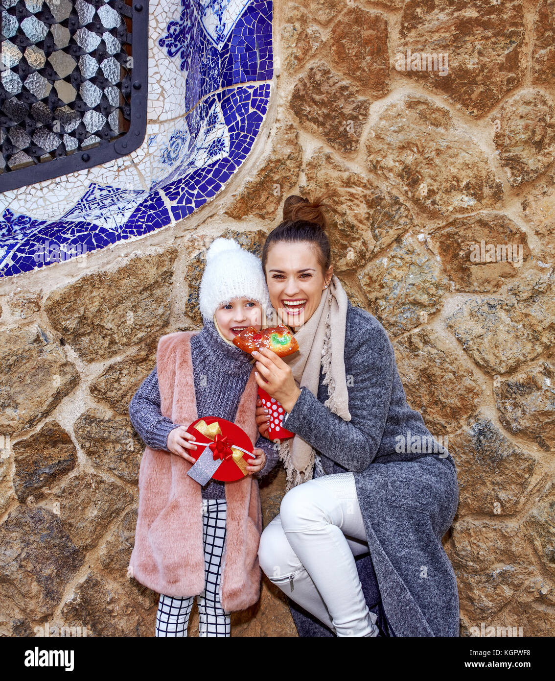 Winter wonderland in Barcelona at Christmas. elegant mother and child travellers in a Santa hat at Guell Park in - Stock Image