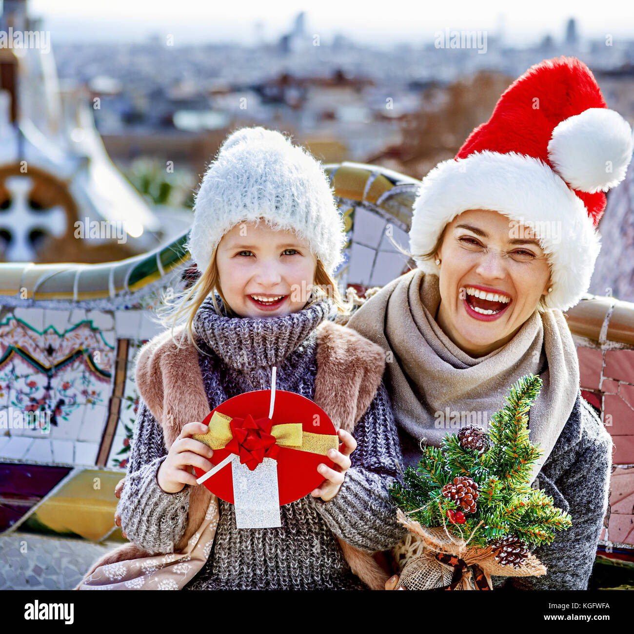 Winter wonderland in Barcelona at Christmas. Portrait of happy trendy mother and child tourists with a little Christmas - Stock Image