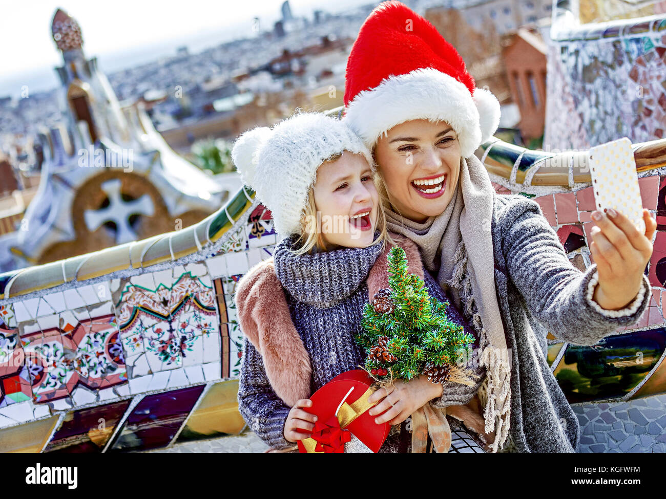 Winter wonderland in Barcelona at Christmas. happy modern mother and child tourists with a little Christmas tree - Stock Image