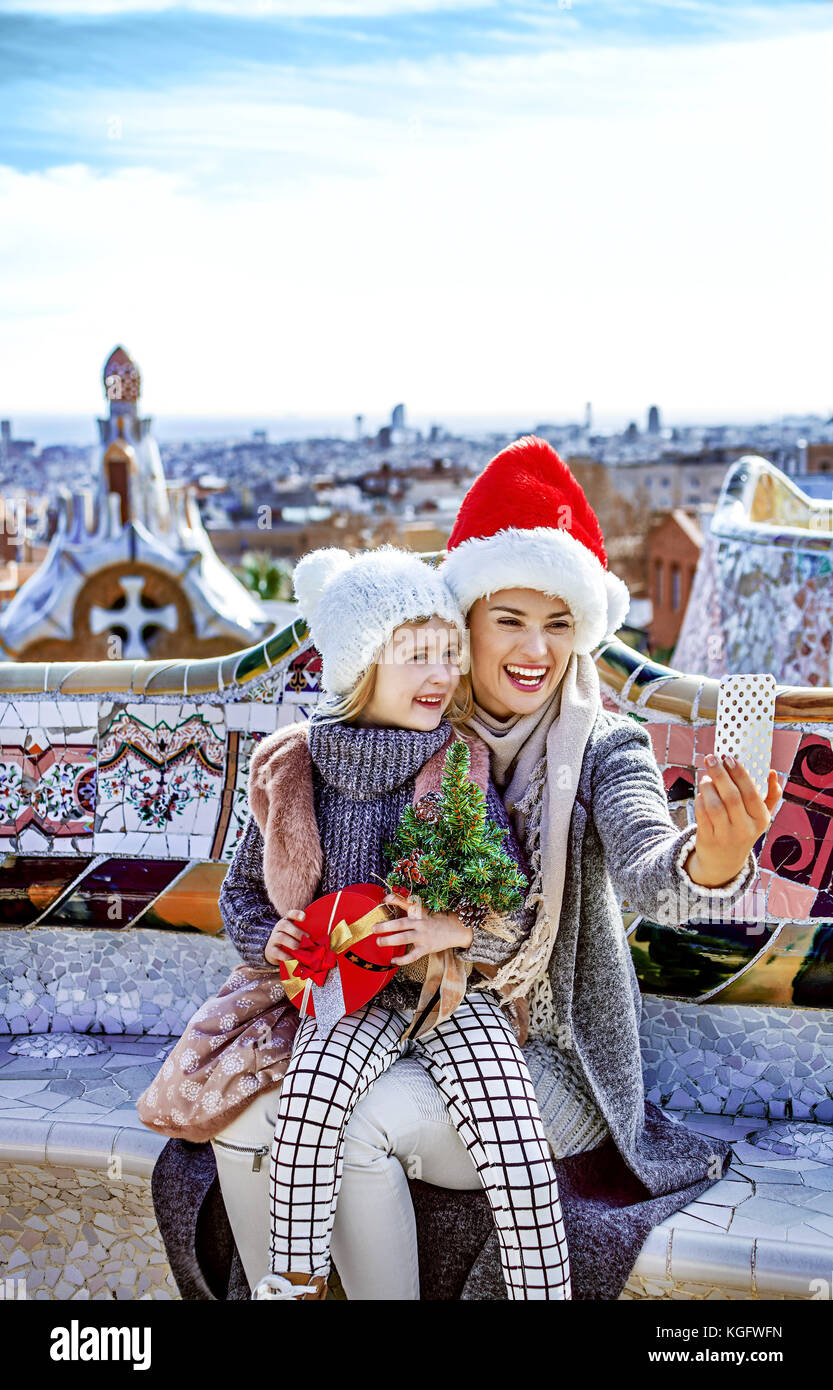 Winter wonderland in Barcelona at Christmas. Portrait of smiling modern mother and child tourists with a little - Stock Image