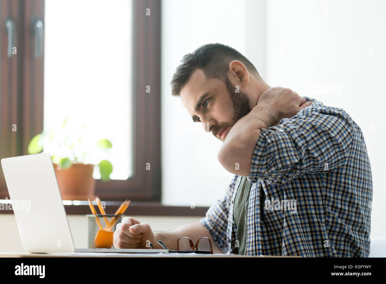 Troubled bearded man massages aching neck with a pained expression, working on laptop computer, deep in thoughts. - Stock Image