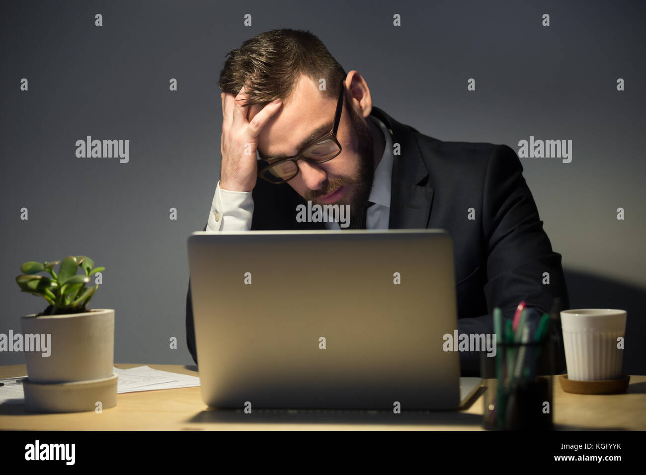 Too much work concept. Troubled man in glasses reading about recent problem on laptop computer, deep in thoughts - Stock Image