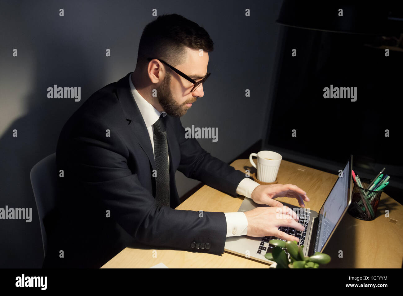 Attentive bearded man in glasses working on project late at night, typing messages, writhing emails using laptop - Stock Image
