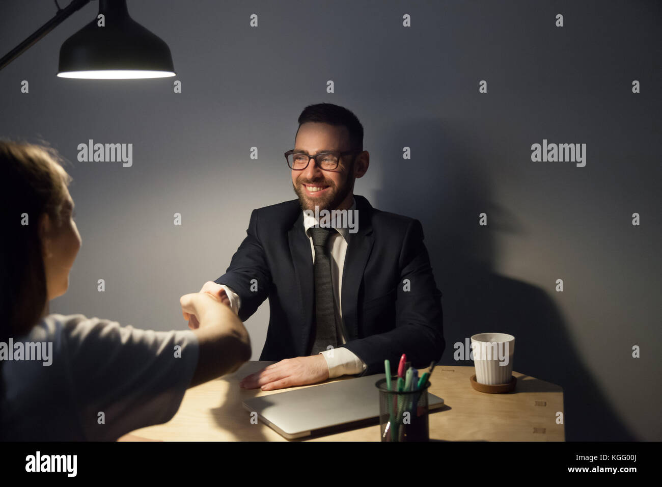 Two businesspeople seal a deal with handshake after long negotiations in dark office with lamp light. Smiling bearded - Stock Image