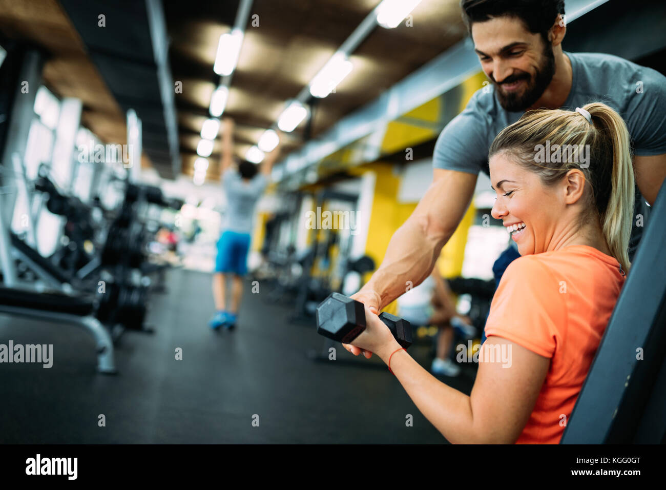 Young beautiful woman doing exercises with personal trainer - Stock Image