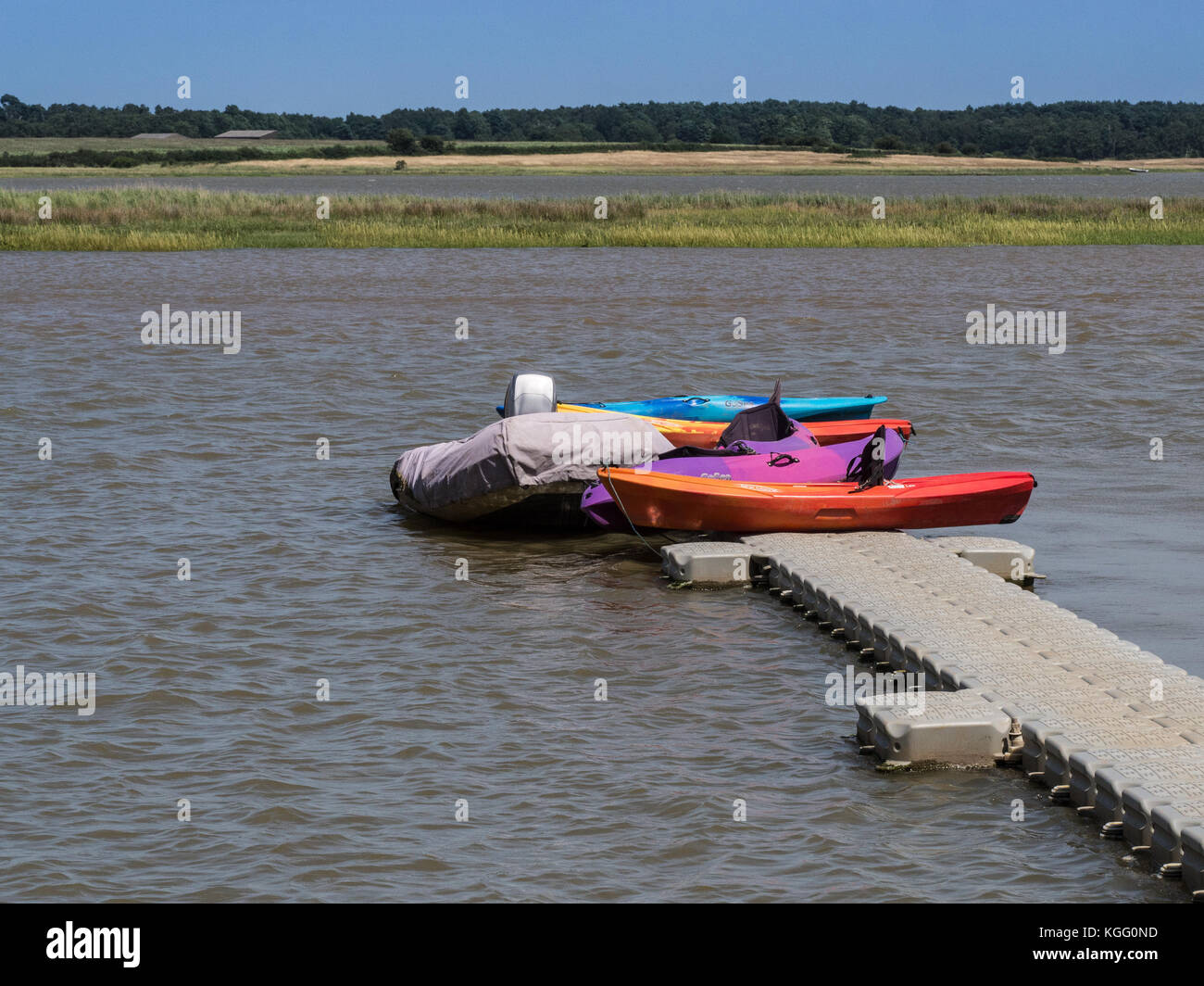 Brightly coloured kayaks on the river Alde at Iken - Stock Image