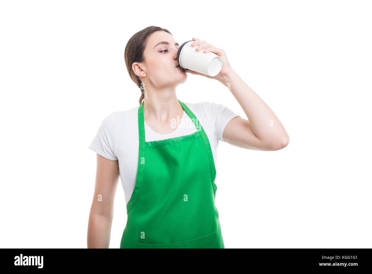Young employer drinking hot disposable coffee or cappuccino on white background - Stock Image