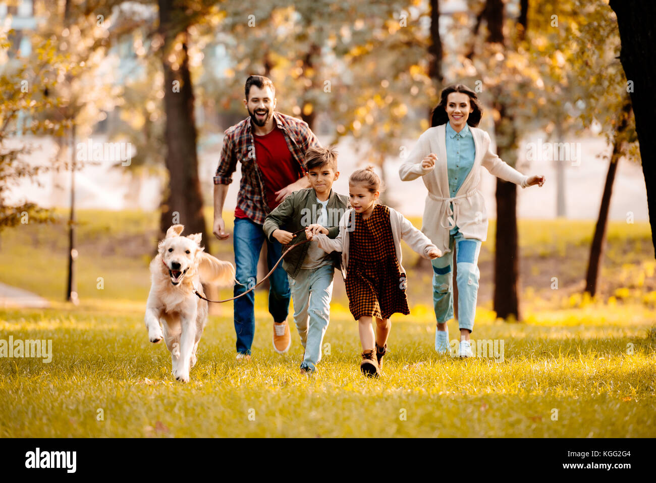 family running with dog in park - Stock Image