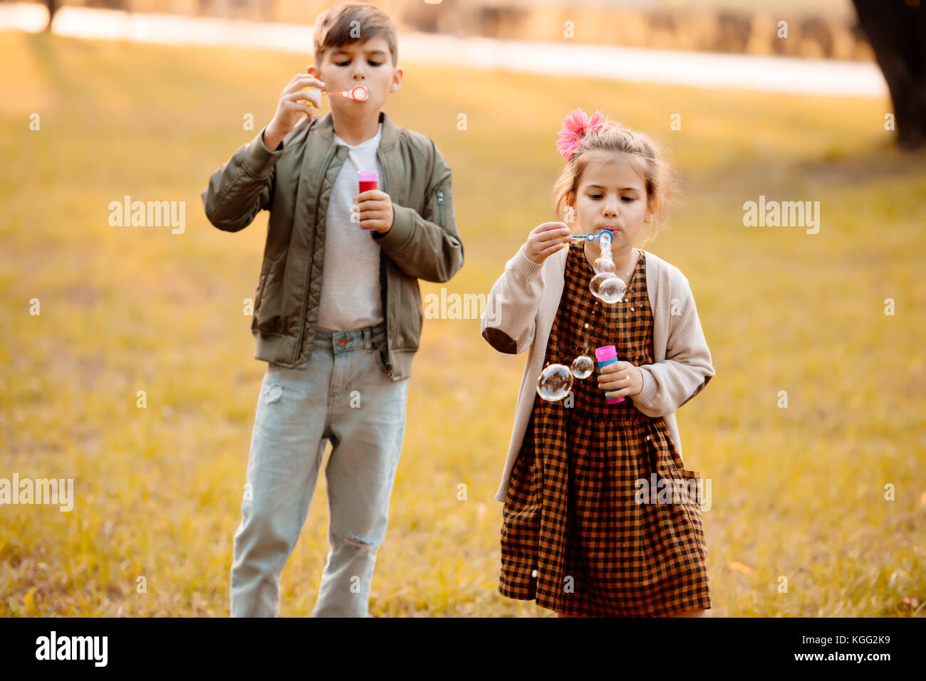 Siblings blowing soap bubbles - Stock Image