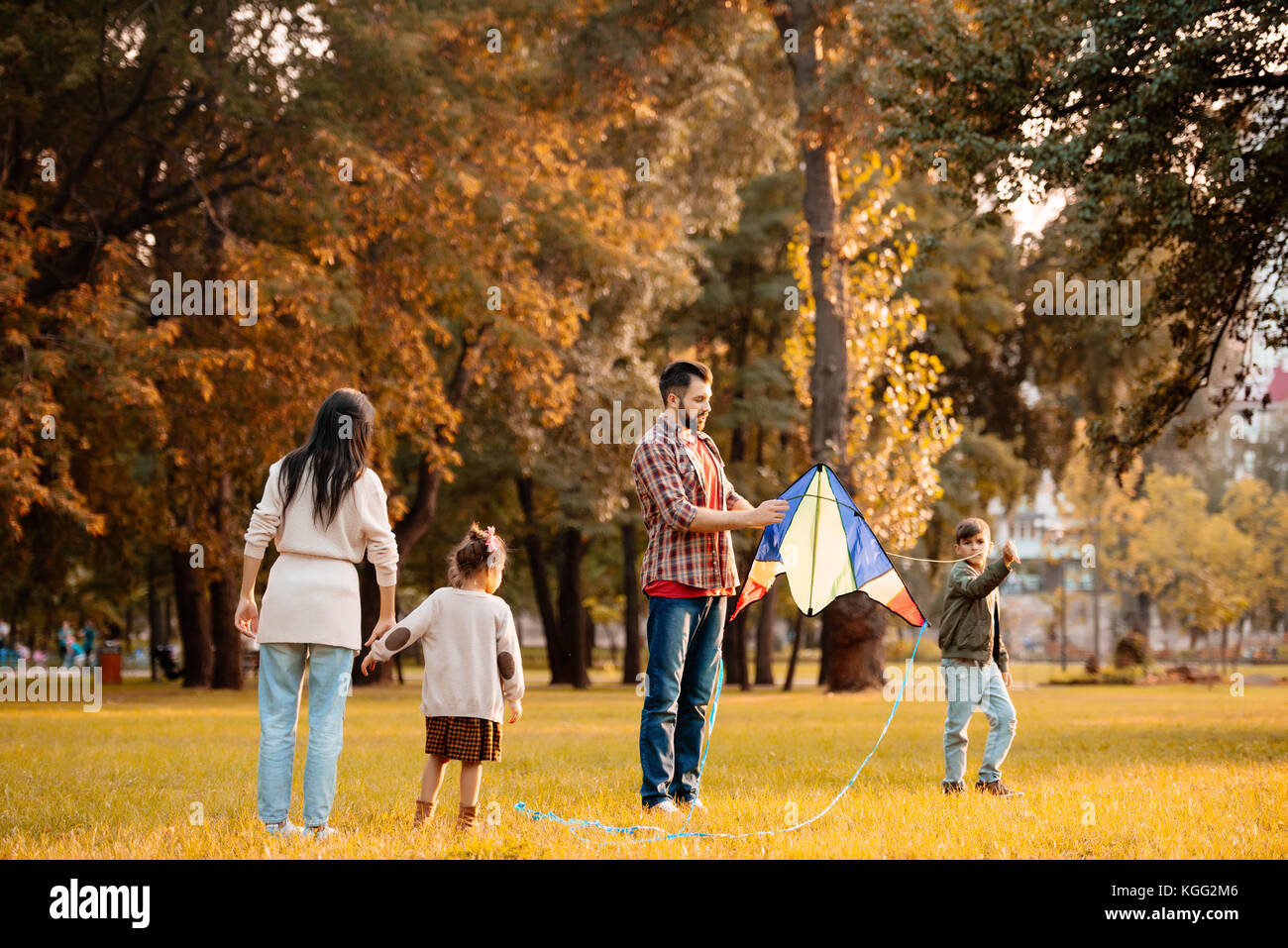 Family flying kite in park - Stock Image