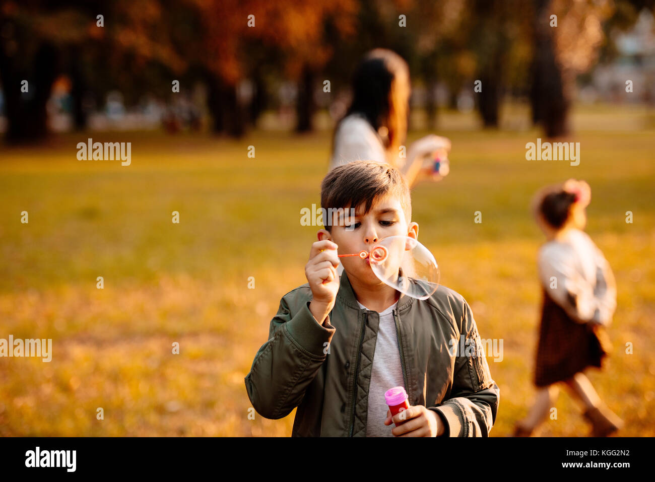 Boy blowing soap bubbles - Stock Image