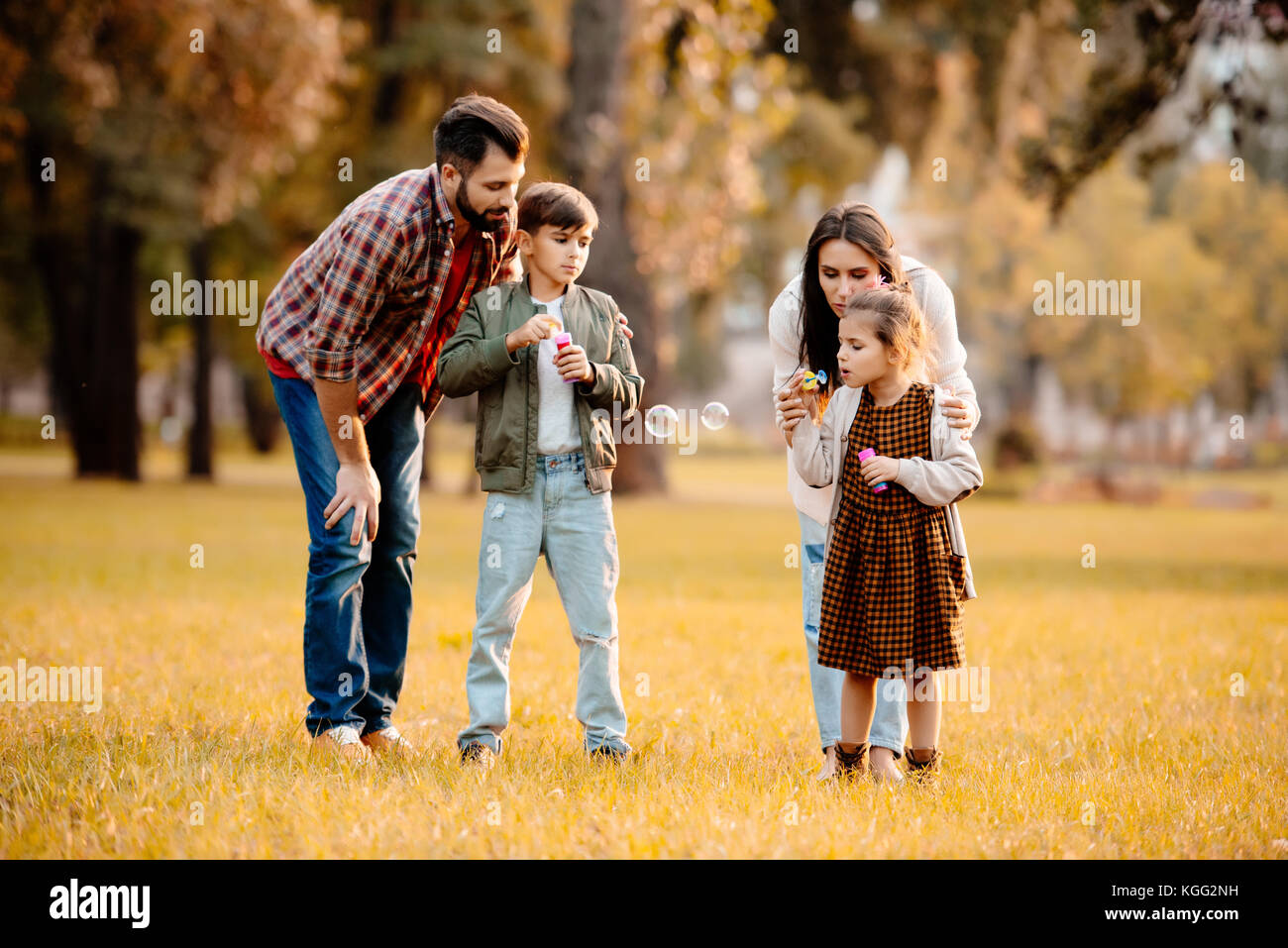 Family blowing soap bubbles - Stock Image