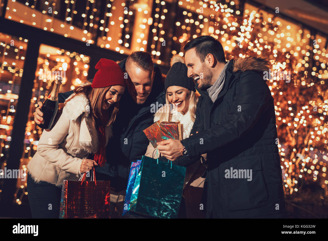 Happy beautiful young couples holding gifts they bought, while standing in mall and checking their shopping bags. - Stock Image