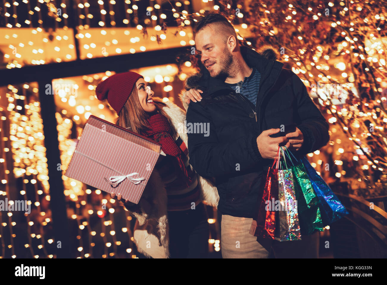 Young couple standing outside with shopping bags and boxes and enjoying an evening stroll through town at Christmas - Stock Image