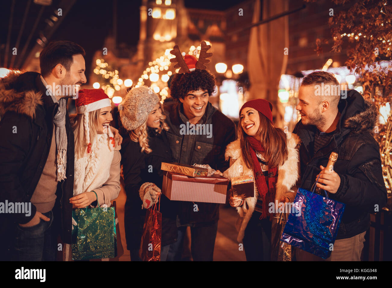 Six smiling young friends standing outside and holding many shopping paper bags, boxes and champagne bottle in city - Stock Image
