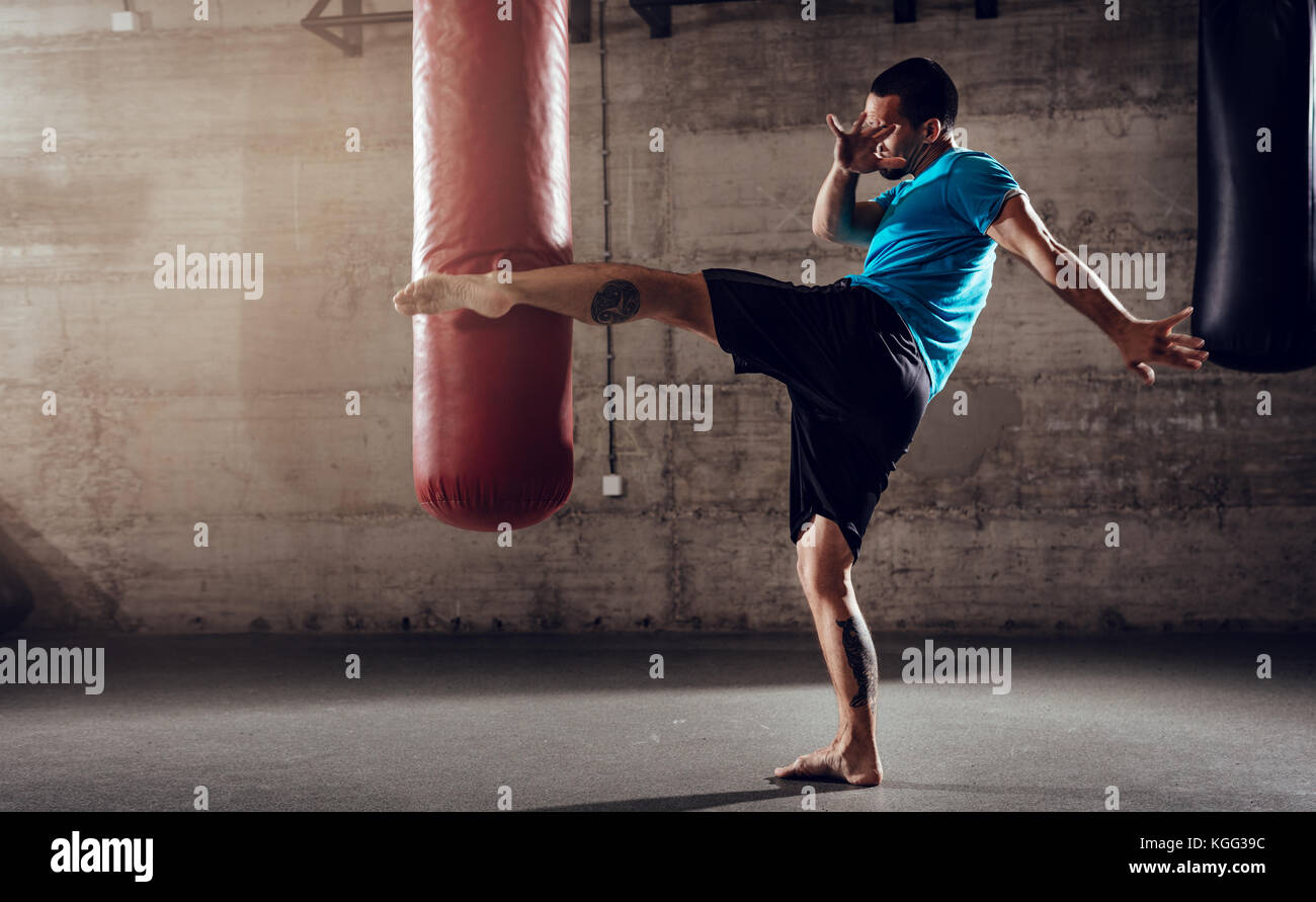 Muscular man punching with leg a boxing bag on cross fit training at the gym. - Stock Image