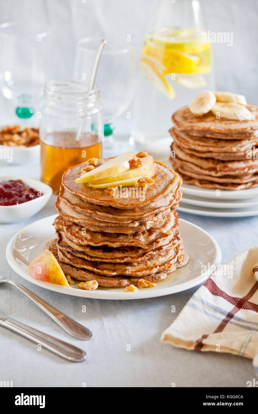 Stack of homemade whole wheat pancakes with fruits and nuts - Stock Image
