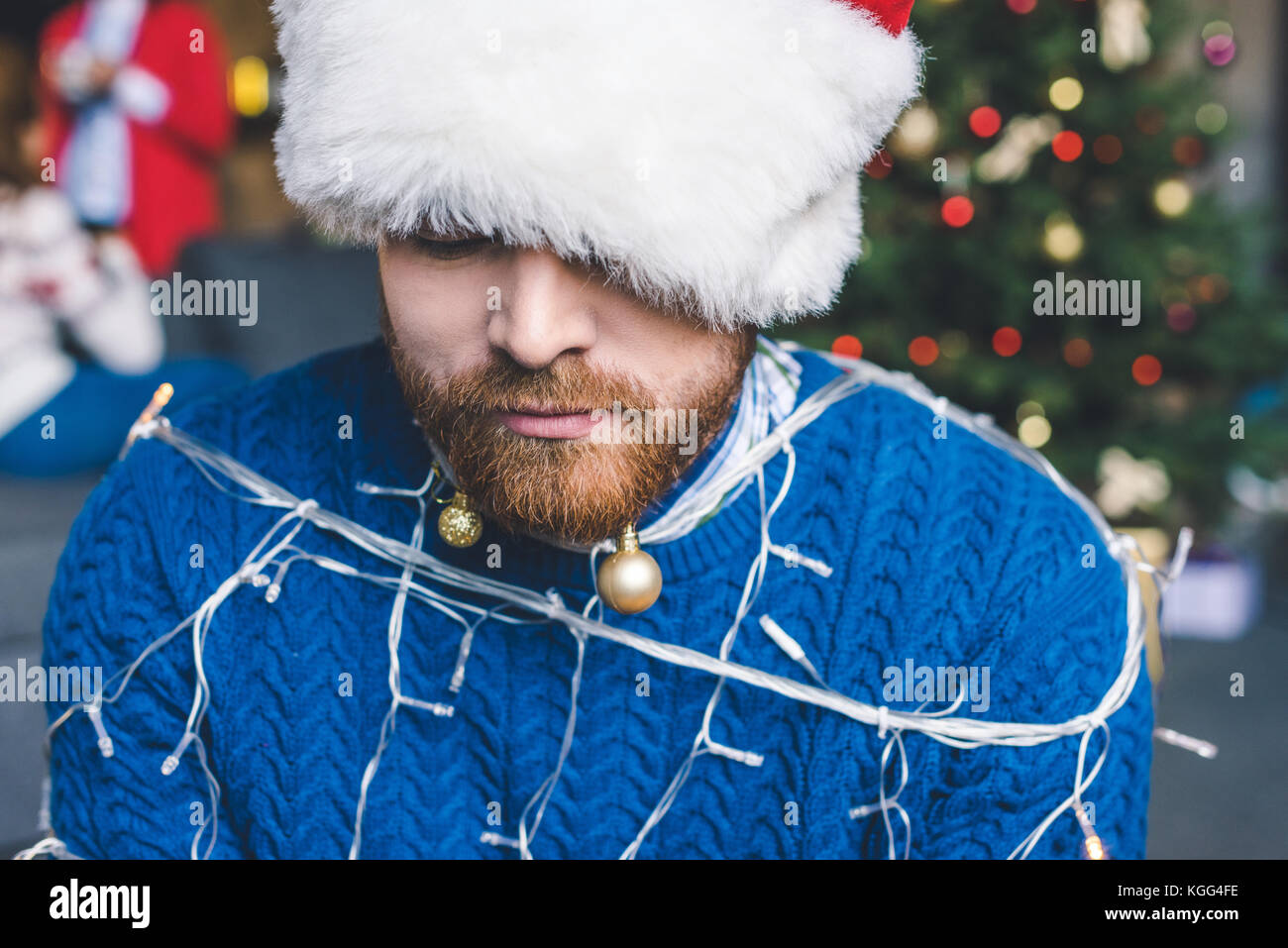 man tied up with christmas garland Stock Photo