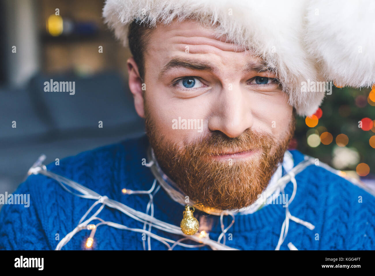 man tied up with christmas garland - Stock Image