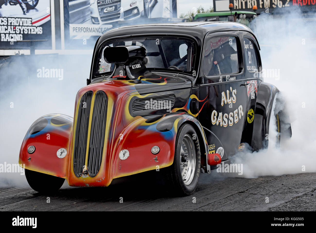 Alan O Connor burn out his Al's Gasser Outlaw Anglia at Santa pod Raceway - Stock Image
