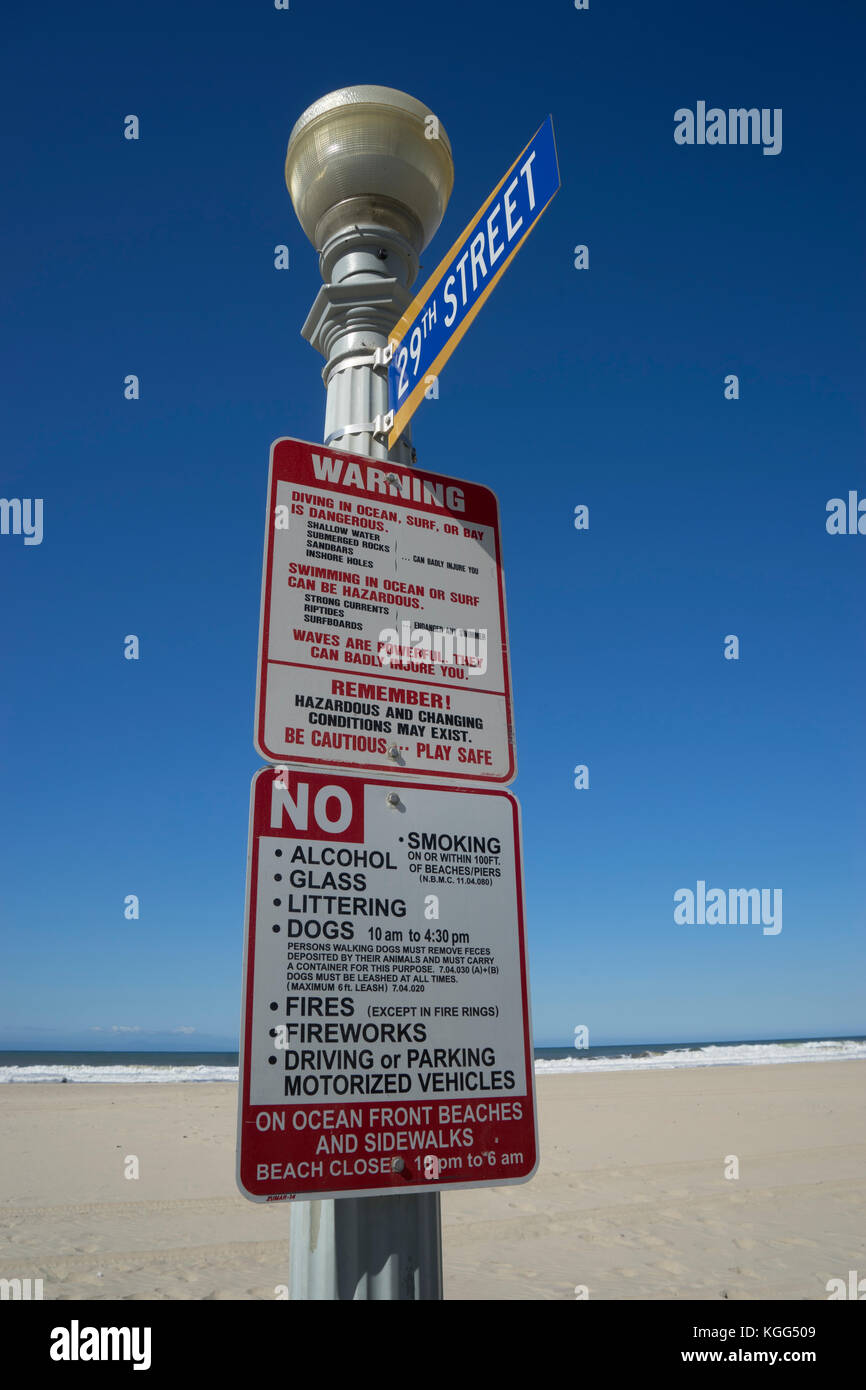 Street light at the beach end of 29th Street with  warning sign about the dangers on the beach plus restrictions - Stock Image
