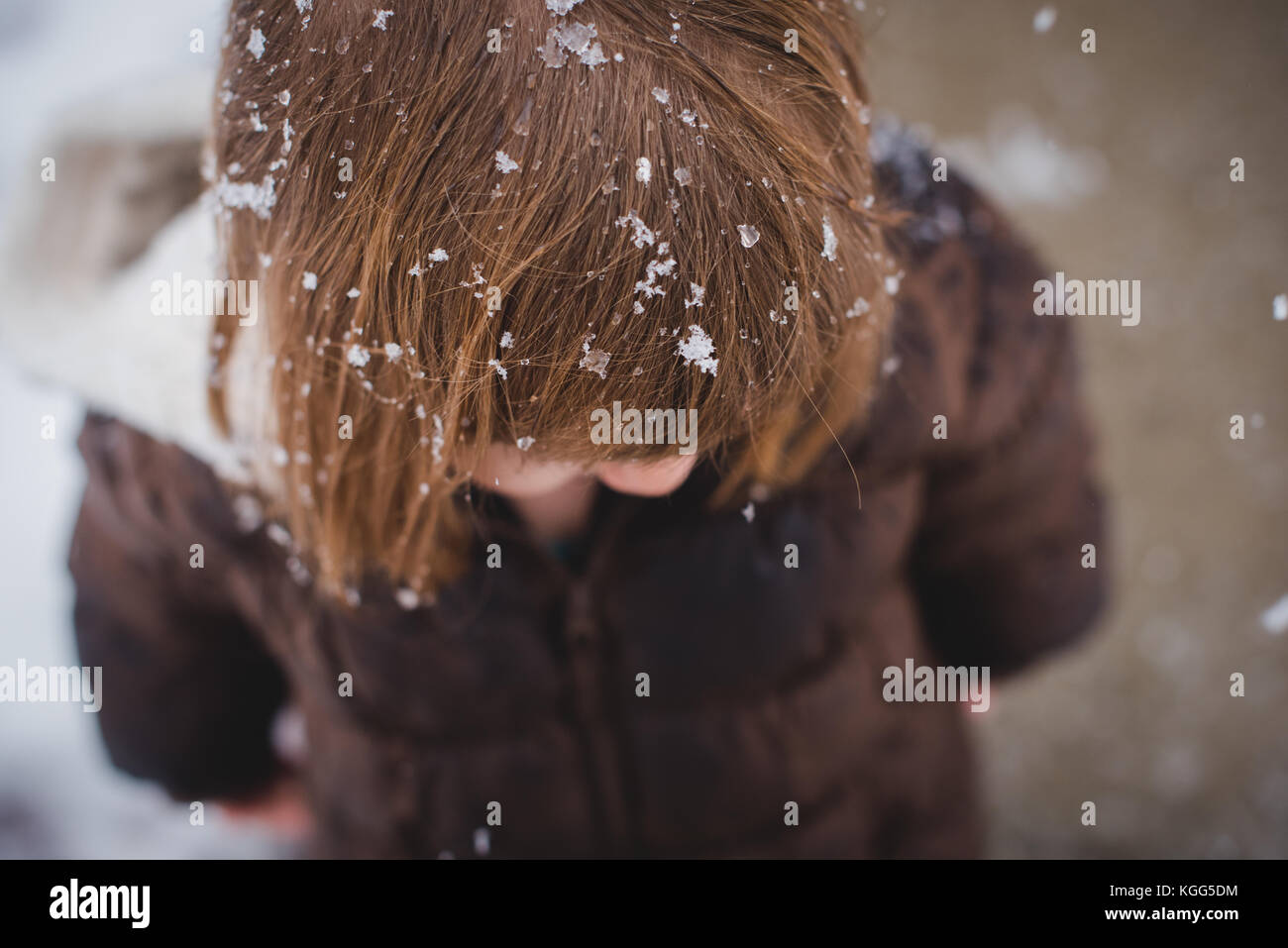 Looking down on a toddler wearing a winter coat with snow in her hair during the winter - Stock Image