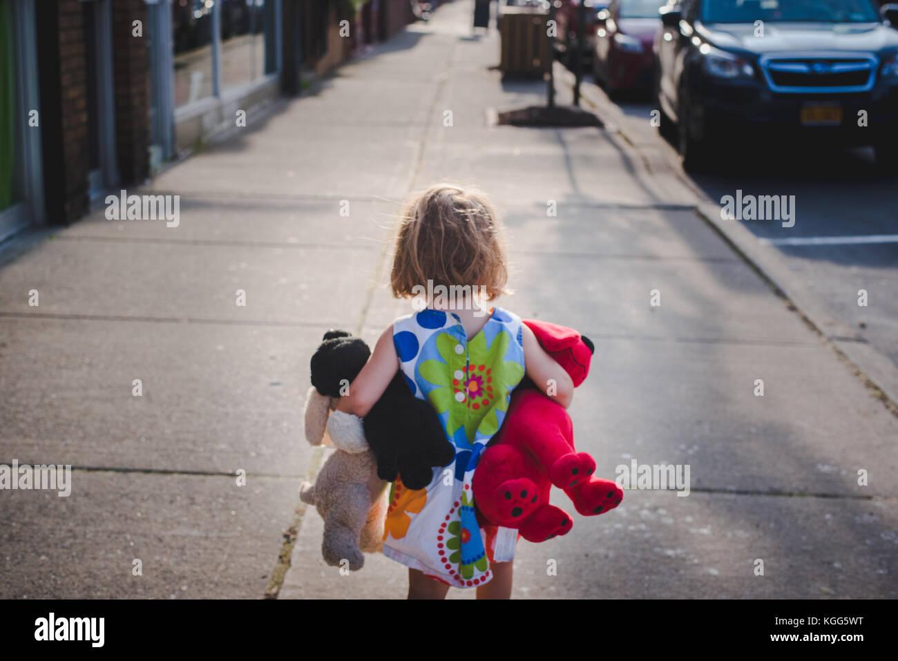 a little girl walks down a sidewalk with a handful of stuffed animals Stock Photo