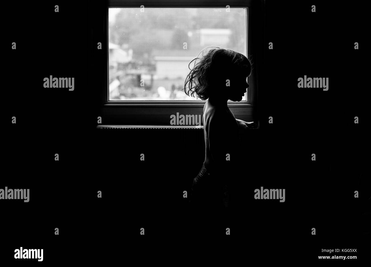 silhouette of a toddler against a window - Stock Image