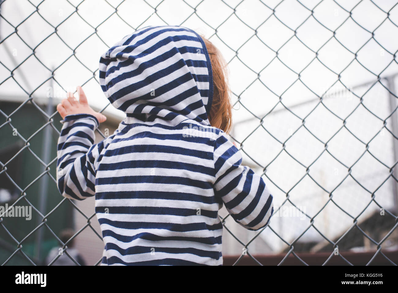 Child hangs on a fence and looks through it. - Stock Image