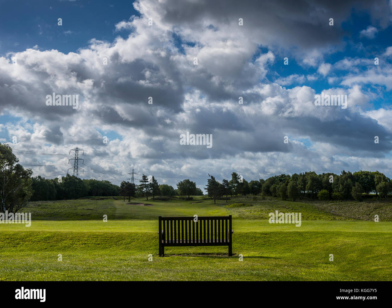 Wooden bench overlooking the sixteenth fairway at Manchester Golf Club, England UK Stock Photo