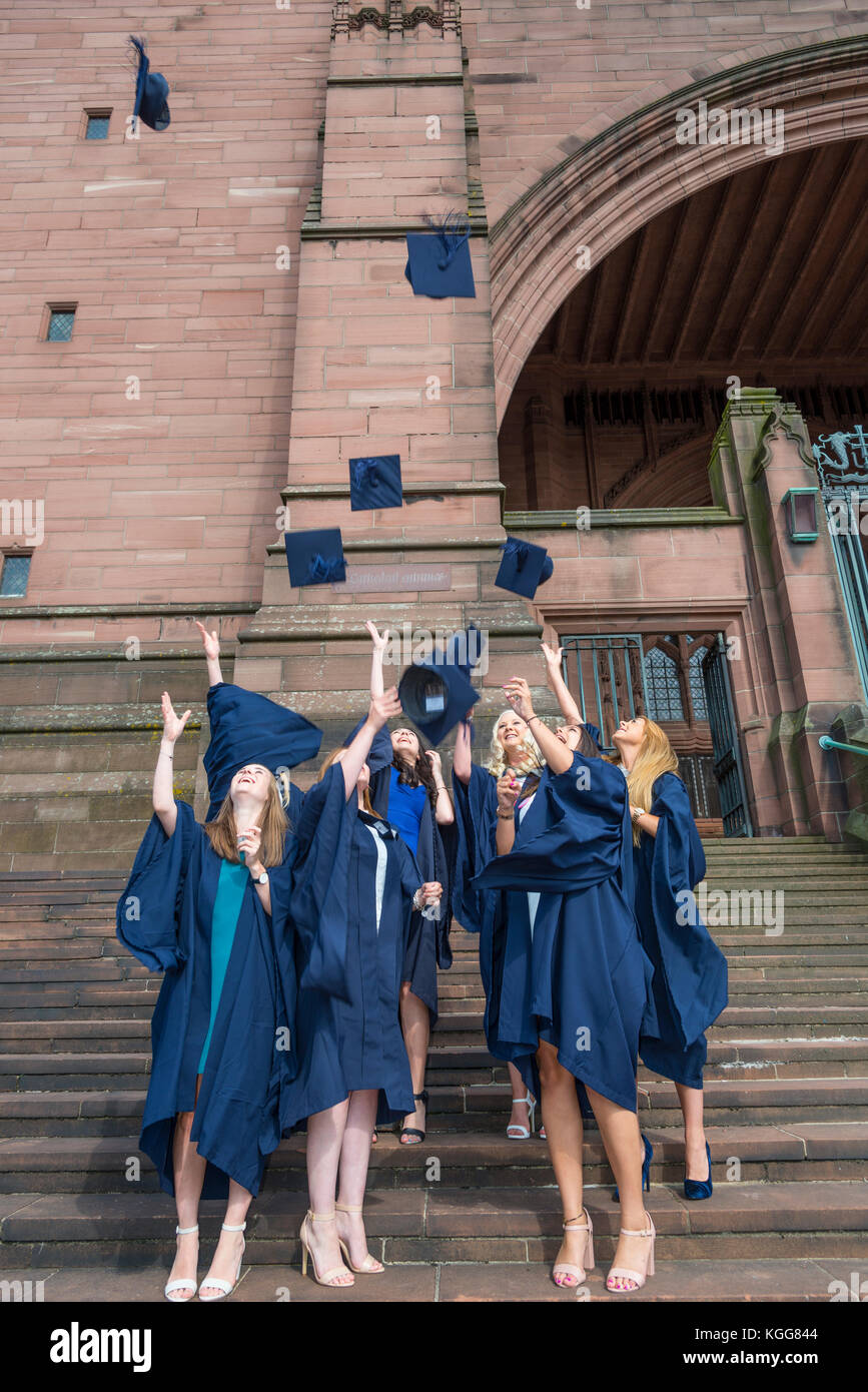 Female graduates celebrating at Liverpool Anglican Cathedral by throwing their mortar boards into the air. - Stock Image