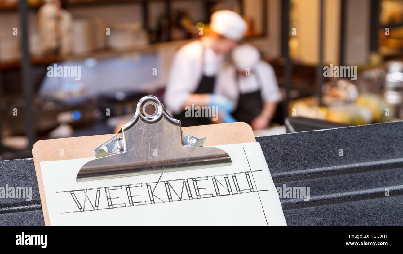 Week menu clipboard with restaurant and two cooks busy blurred in the background. Stock Photo