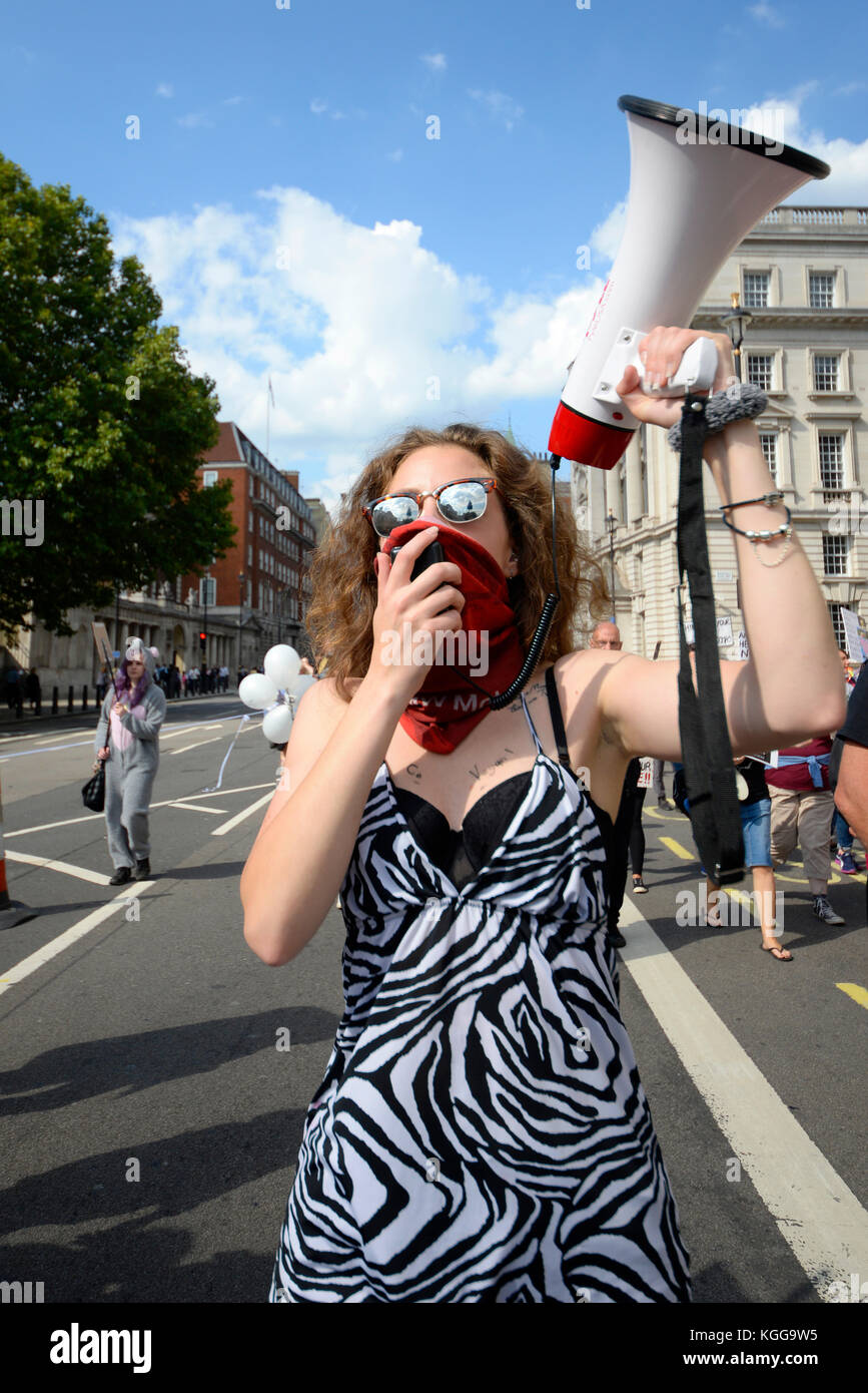Female vegan activist shouting through megaphone loud hailer in Whitehall London during an animal rights protest - Stock Image