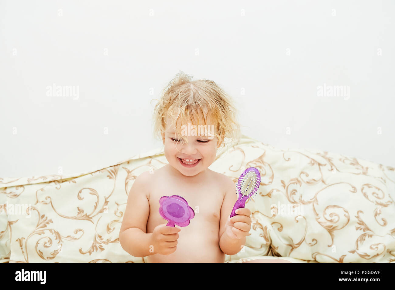 Smiling baby girl after a bath with child comb and mirror brushing her hair sitting in the bed. Selective focus, - Stock Image