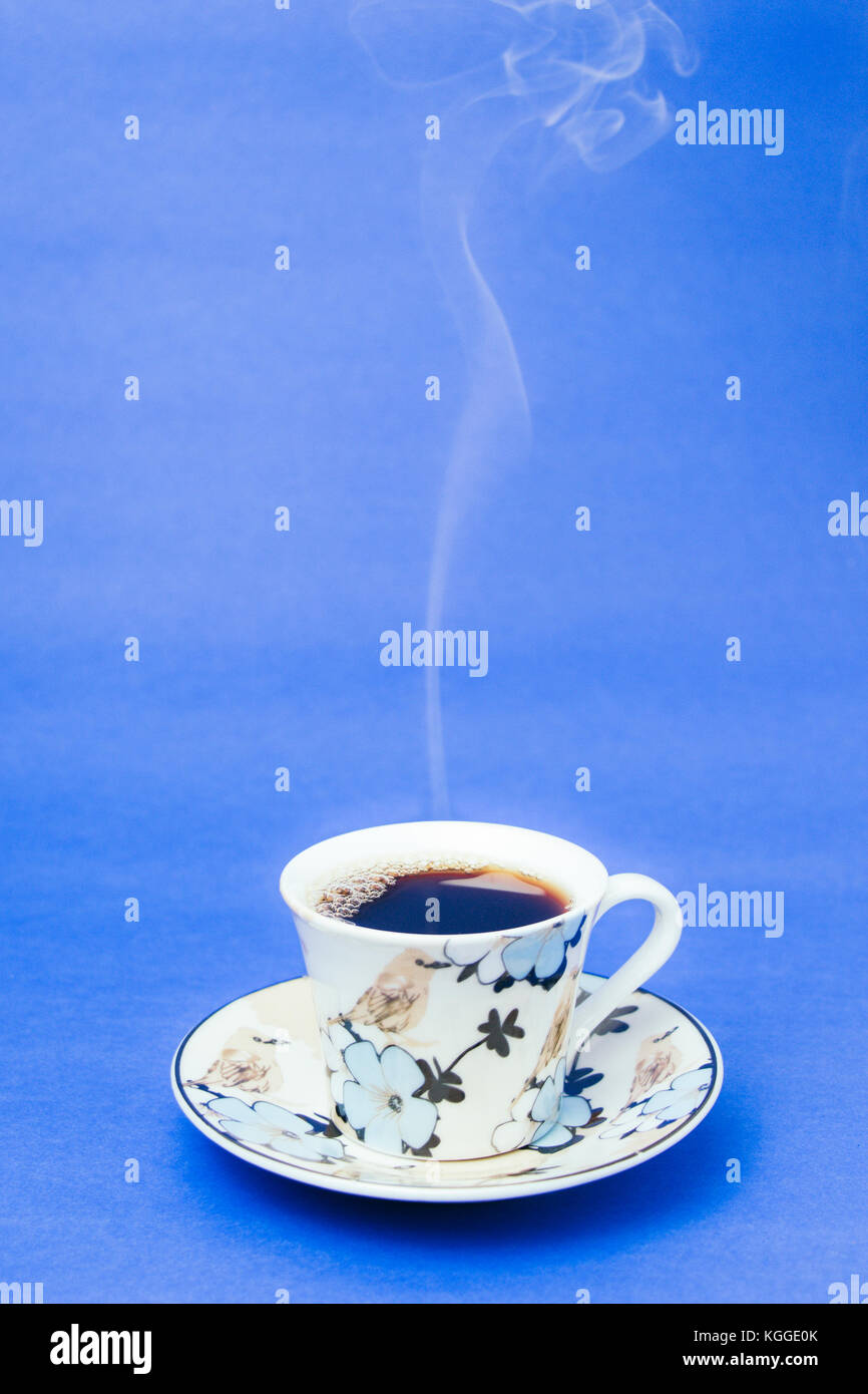 Blue stamped mug with steaming coffee. Soft smoke. Blue background. Vertical photo - Stock Image