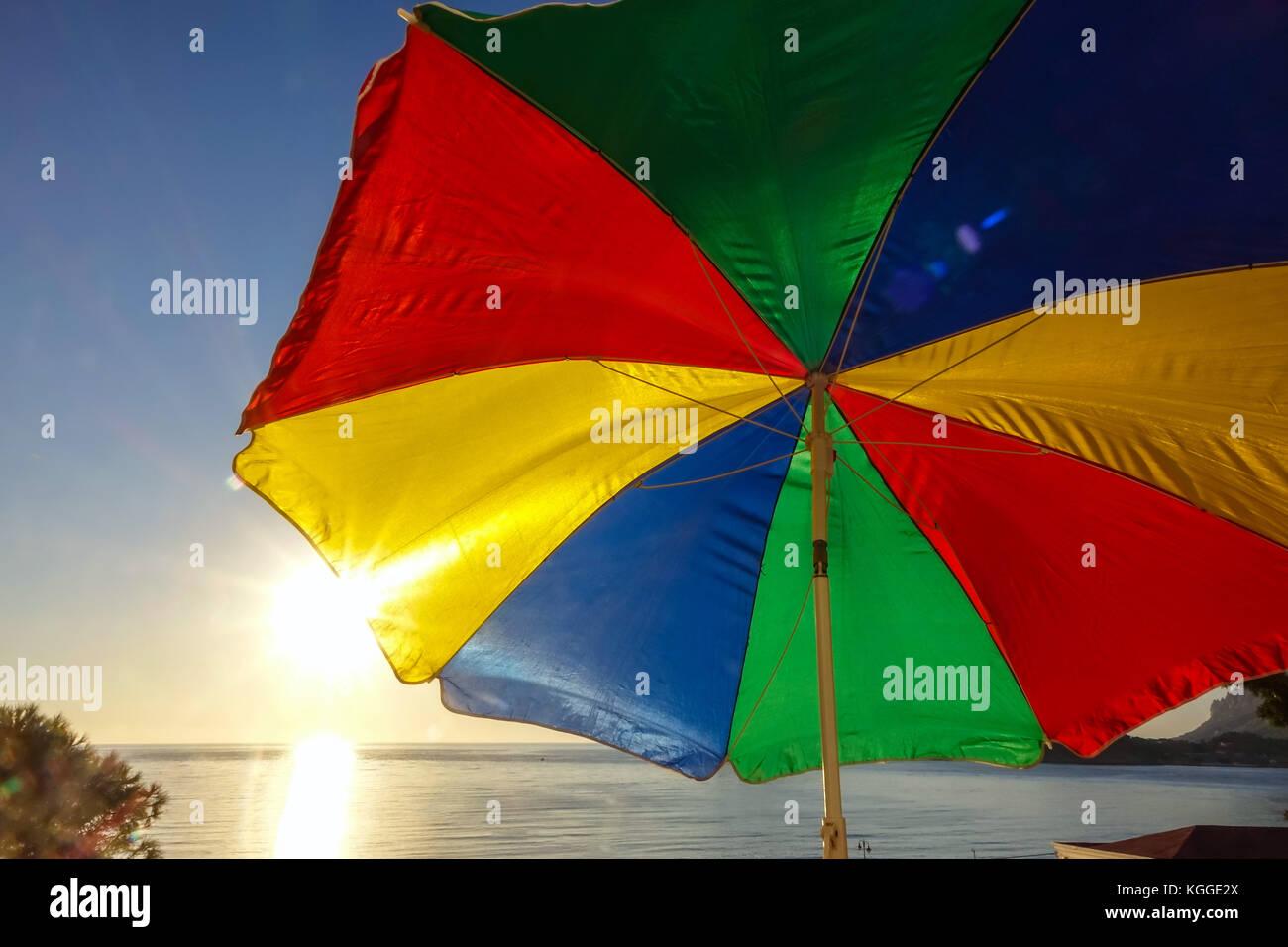 e80eced9a4f0 Rainbow coloured sun umbrella at the beach backlit against clear blue sky,  Kalymnos, Greece