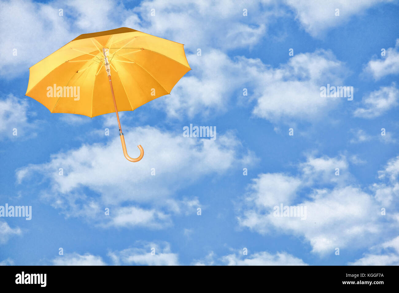 Mary Poppins Umbrella.Yellow umbrella flies in sky against of white clouds.Wind of change concept. - Stock Image