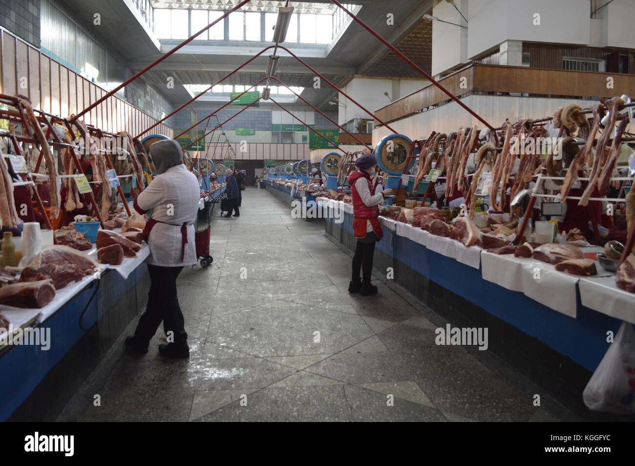 local indoor bazaar in Almaty, Kazakhstan, with red raw meat on display: cow, sheep, camel, pig. Sausages, kolbasa. - Stock Image