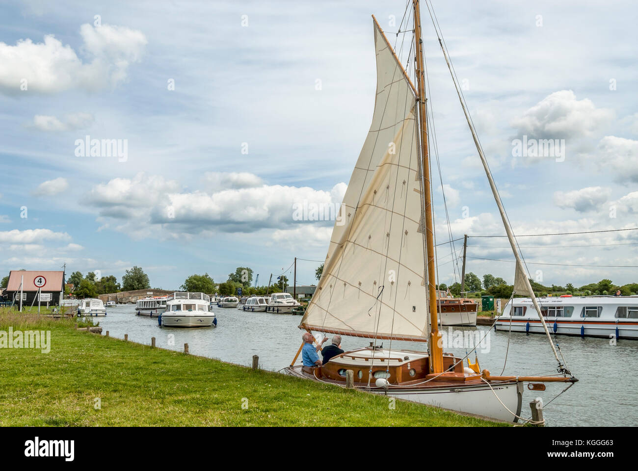 Traditional wooden sailing boat at The Broads is a large network of mostly navigable rivers and lakes in the English Stock Photo