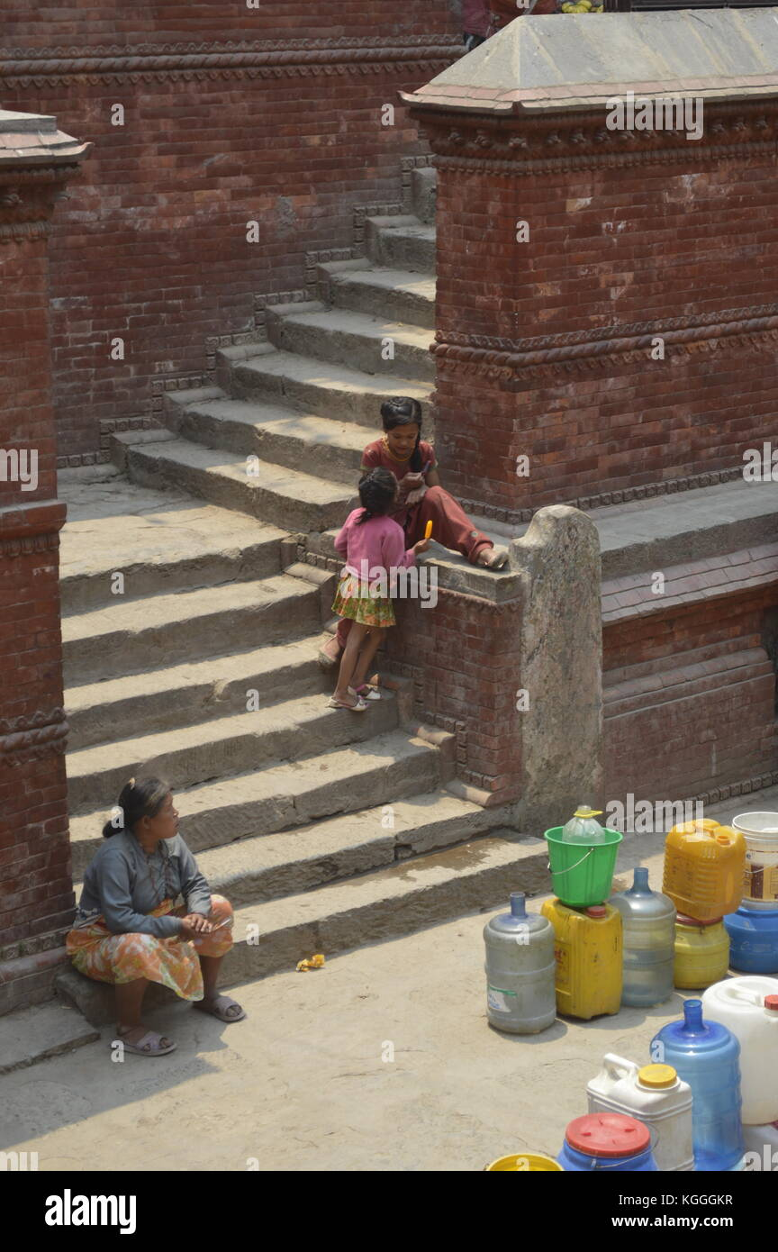 Nepalese people waiting to collect drinking water with jerrycan in ancient fountain, Kathmandu, Nepal. water shortage, - Stock Image
