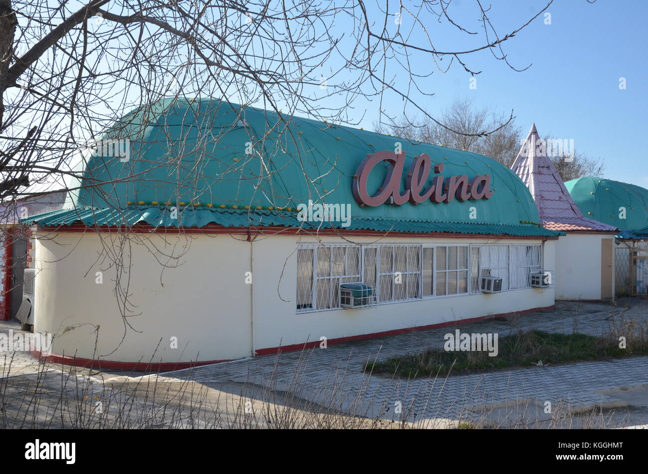 Alina, the name of a shop in Aktau, Kazakhstan close to the Caspian sea. restaurant. abandoned. winter. - Stock Image