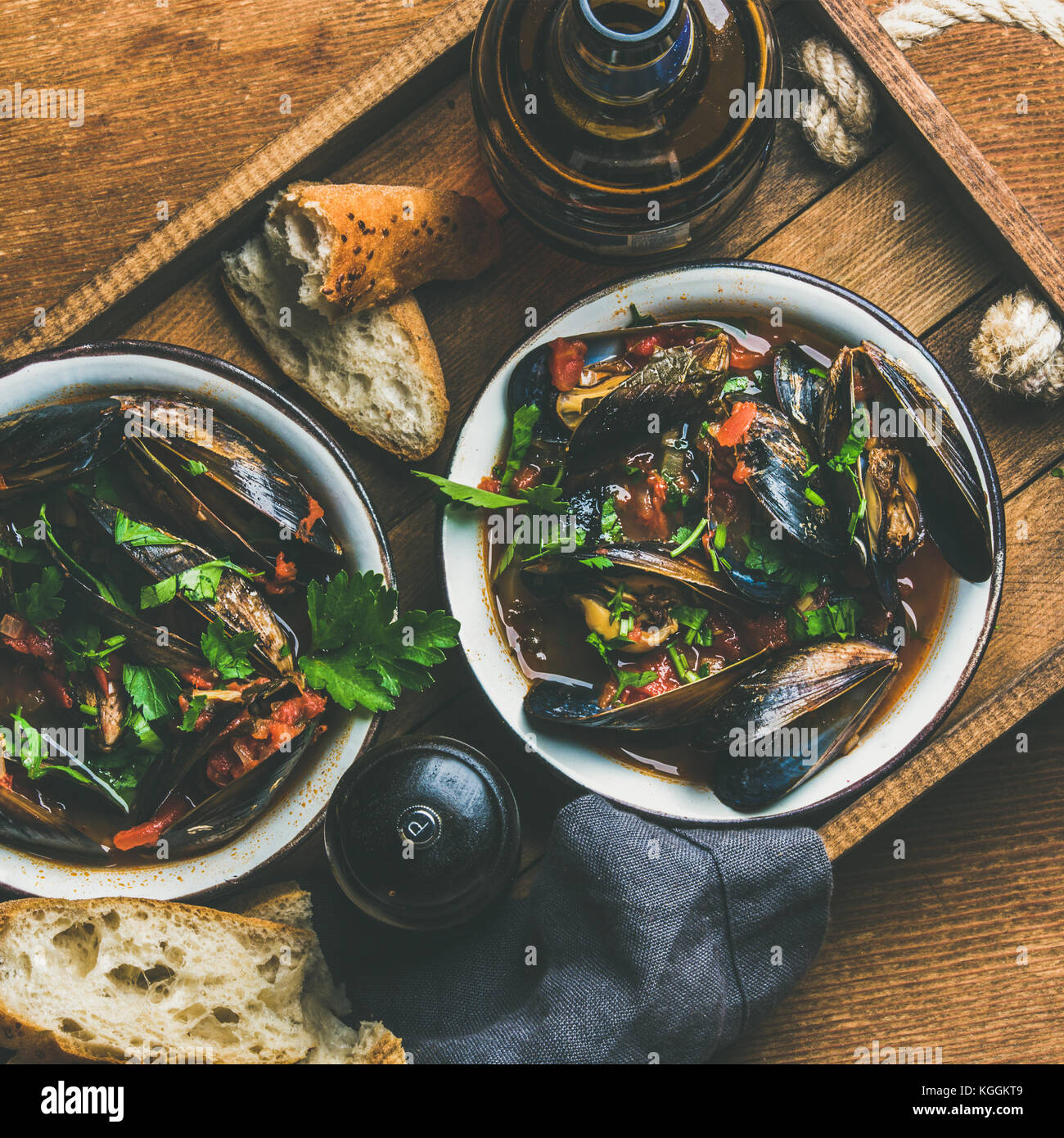 Belgian boiled mussels in tomato sauce with parsley in tray - Stock Image