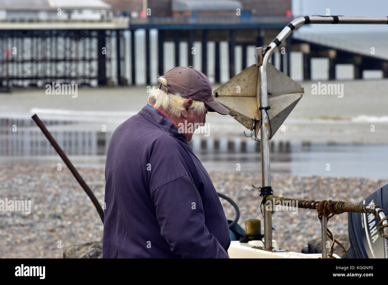 an old fisherman on the beach at Cromer in Norfolk reminiscing about days gone by. Elderly fisherman wearing a cap - Stock Image