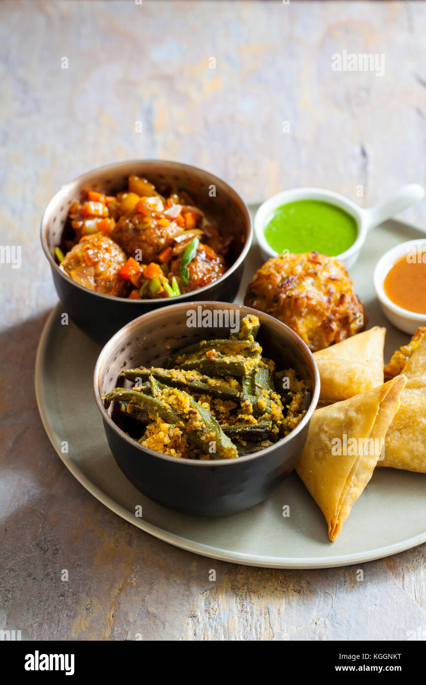 Selection of Indian dishes: samosas, onion bhaji, manchurian balls and okra - Stock Image