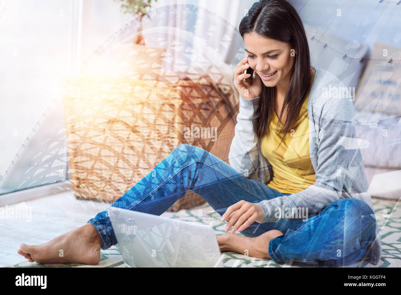 Pleasant conversation. Cheerful nice young woman sitting comfortably on the floor and looking at the screen of her Stock Photo