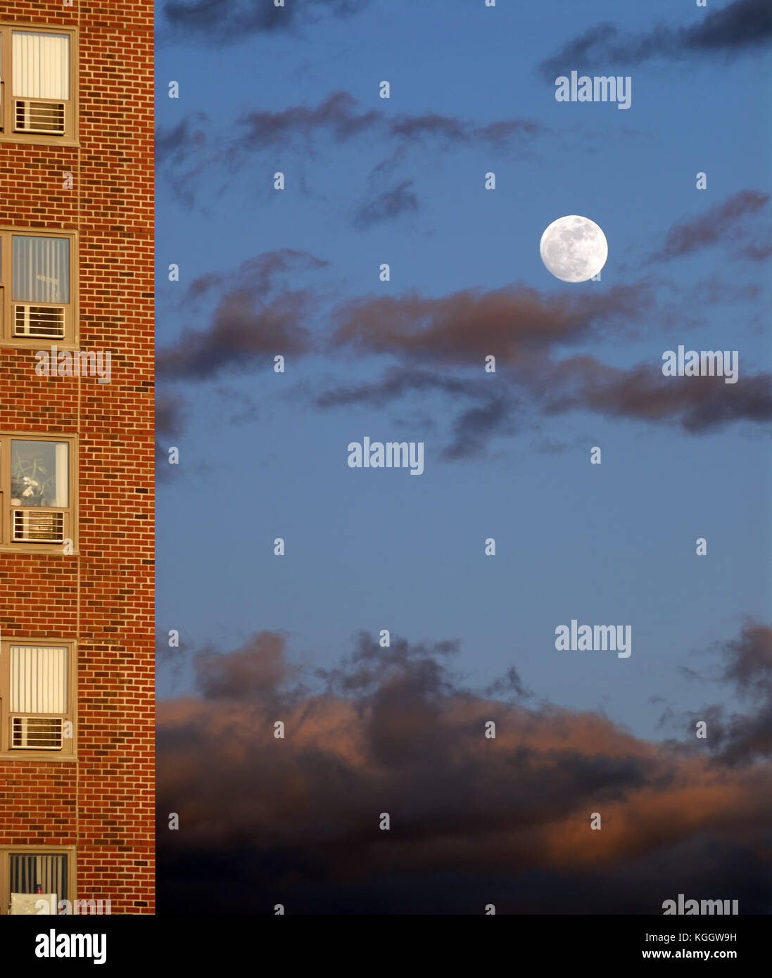 Full moon rising by the public housing project. Abstract background for low income family dreams, aspirations… Stock Photo